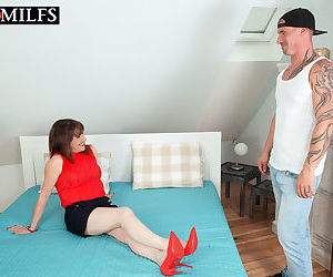 Older woman seduces a man with her great legs in shorts..
