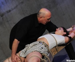 Rope bound female is relieved of her clothes before being..